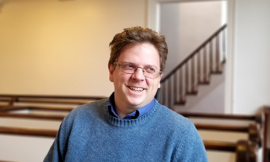 A man sitting in a church pew and smiling