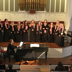 A young women's choir singing while a pianist plays.