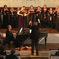 A young women's choir is accompanied by a violist