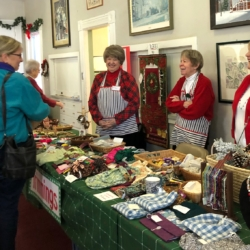 Women smile and chat with a customer looking at handmade goods