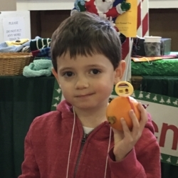 A boy shows off his completed Christingle