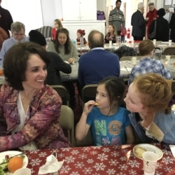 A woman and two children eating lunch at the Advent potluck