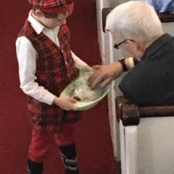 A boy passes out dried fruit as part of the Christingle service