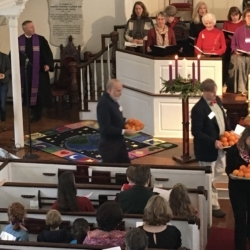 People pass out oranges as part of the Christingle service