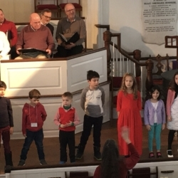 A group of children sing in a church