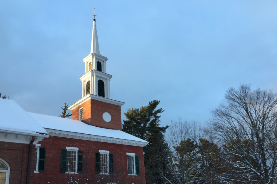 Sunlight strikes the steeple of the brick church in winter
