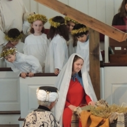 The wise men kneel before the manger. Mary adores the baby Jesus while children dressed as angels look on.