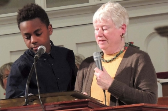 A middle-aged woman and teenage boy read from the Bible