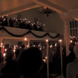 The sanctuary lit by candles held by congregants as they sing Silent Night.