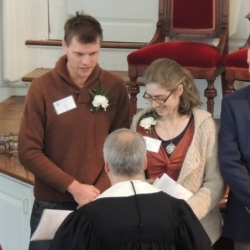 The pastor shakes the hands of a young married couple to welcome them into the church