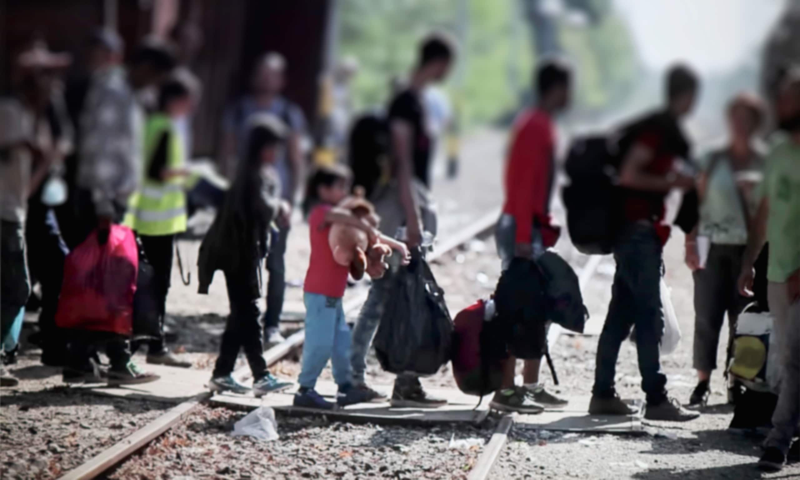 Refugees crossing train tracks