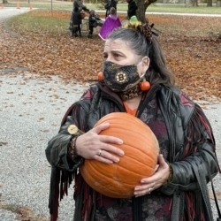 A woman dressed as a cat holds a pumpkin