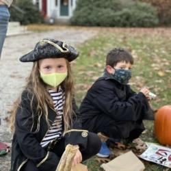 A girl dressed as a pirate decorates a pumpkin