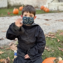 A boy in costume waves while decorating his pumpkin